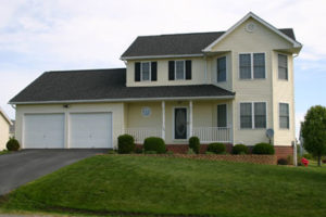 A yellow two-story Colonial house with a garage in Ranson, WV.