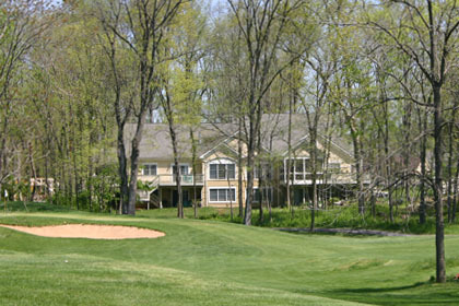 A two-story house shrouded by trees and overlooking the Cress Creek golf course.