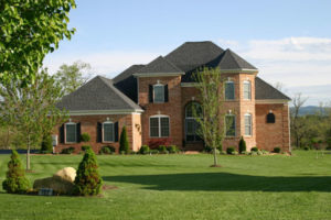 A two-story brick house with bay windows, a large lawn and beautiful landscaping.