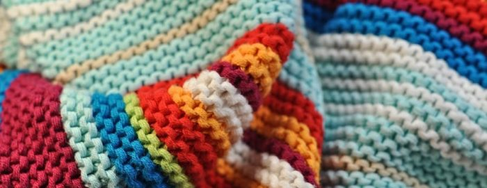 A large blanket knitted from multi-colored wool.