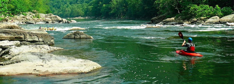 A green river containing boulders, gentle rapids, and a group of kayakers.
