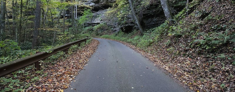 A narrow paved road sandwiched between mountain cliffs and a metal railing.