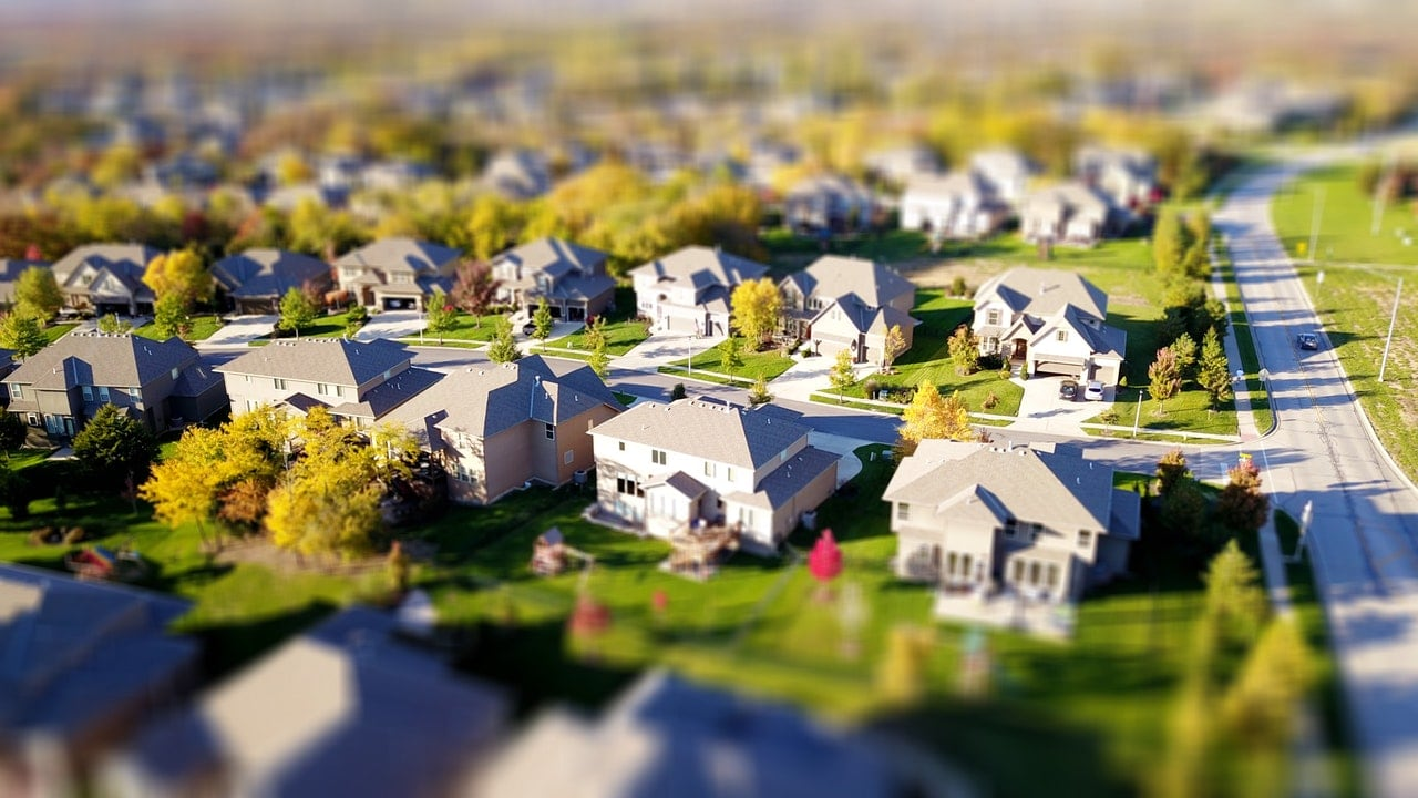 Aerial drone shot of a neighborhood with large white houses.