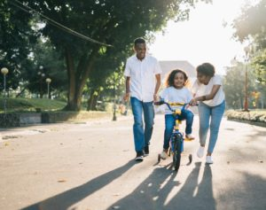 Two parents pushing their daughter as she rides a bike for the first time.