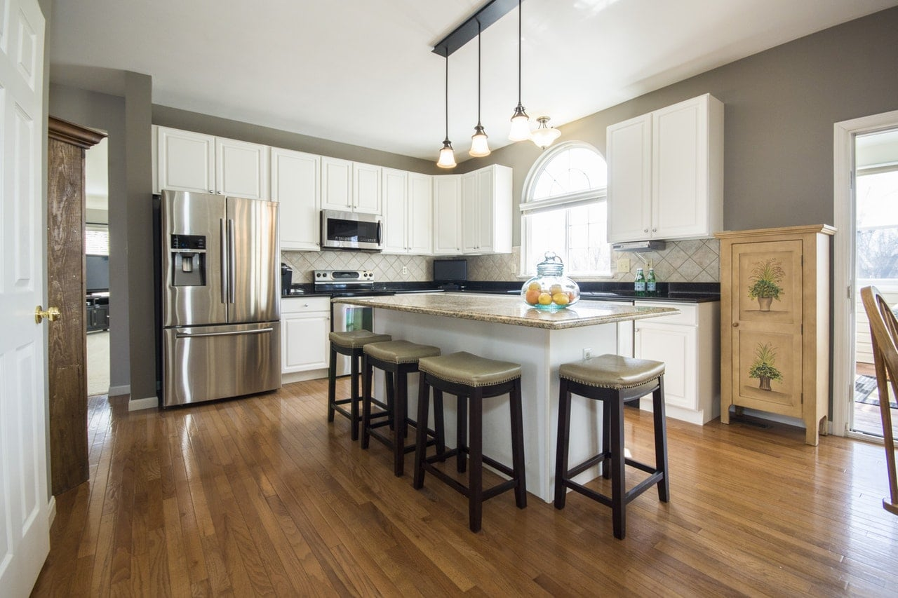 Modern kitchen interior with bar seating and hardwood floors.