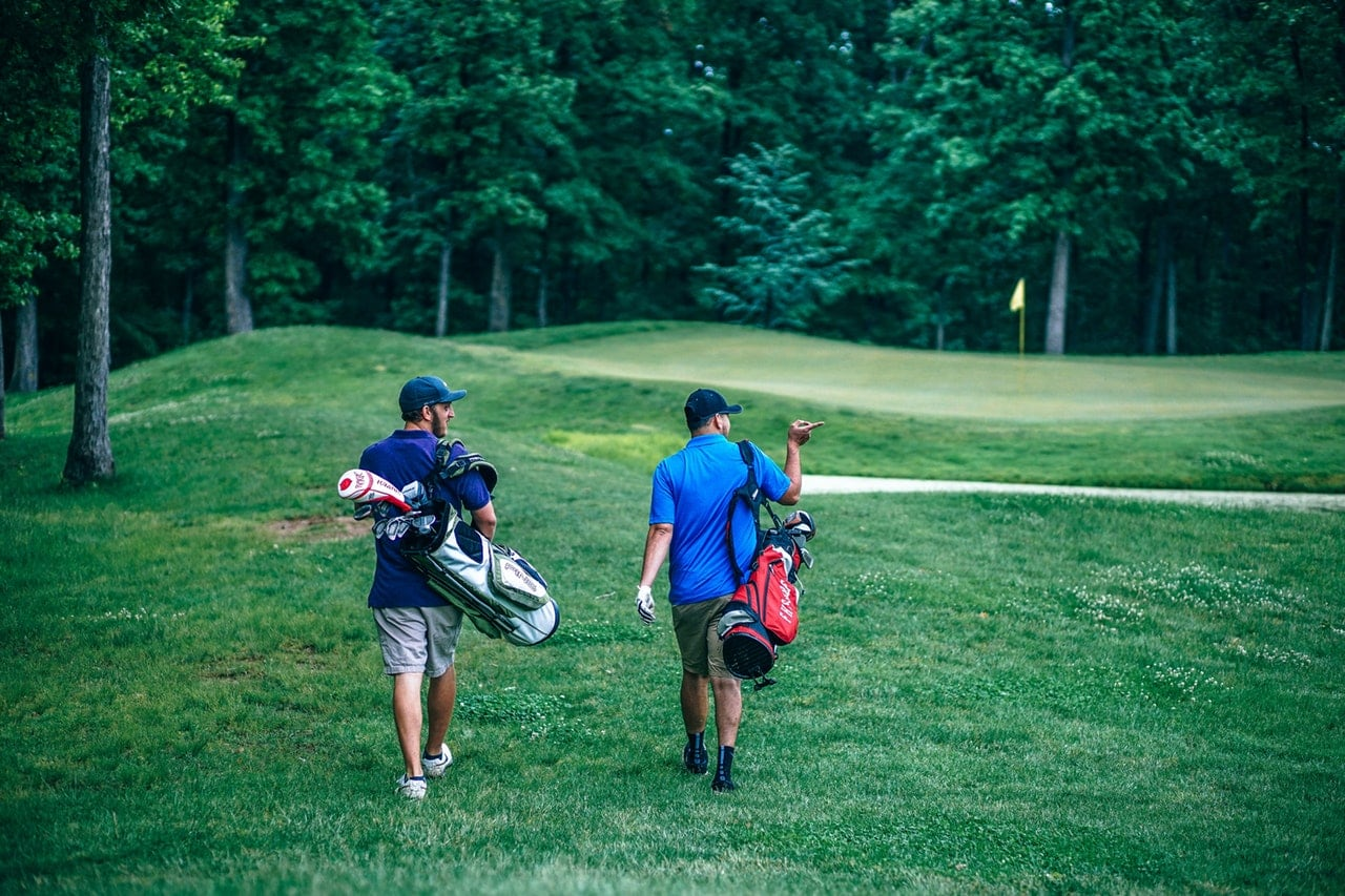 Two men walking across a golf course carrying their bags.