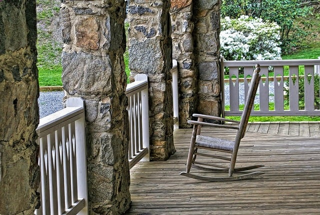A wooden rocking chair sitting on a front porch with stone pillars.