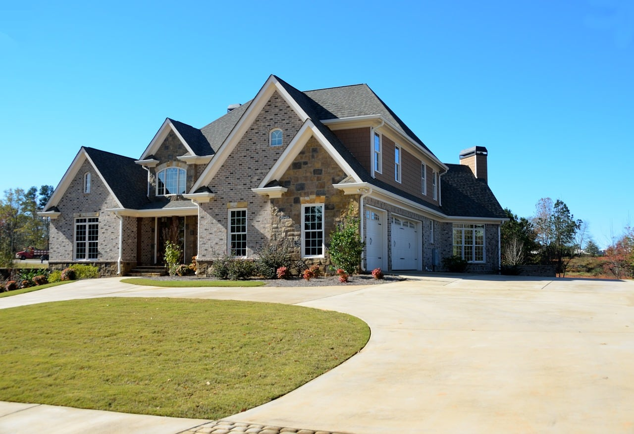 A luxury two-story brick home with a huge driveway.