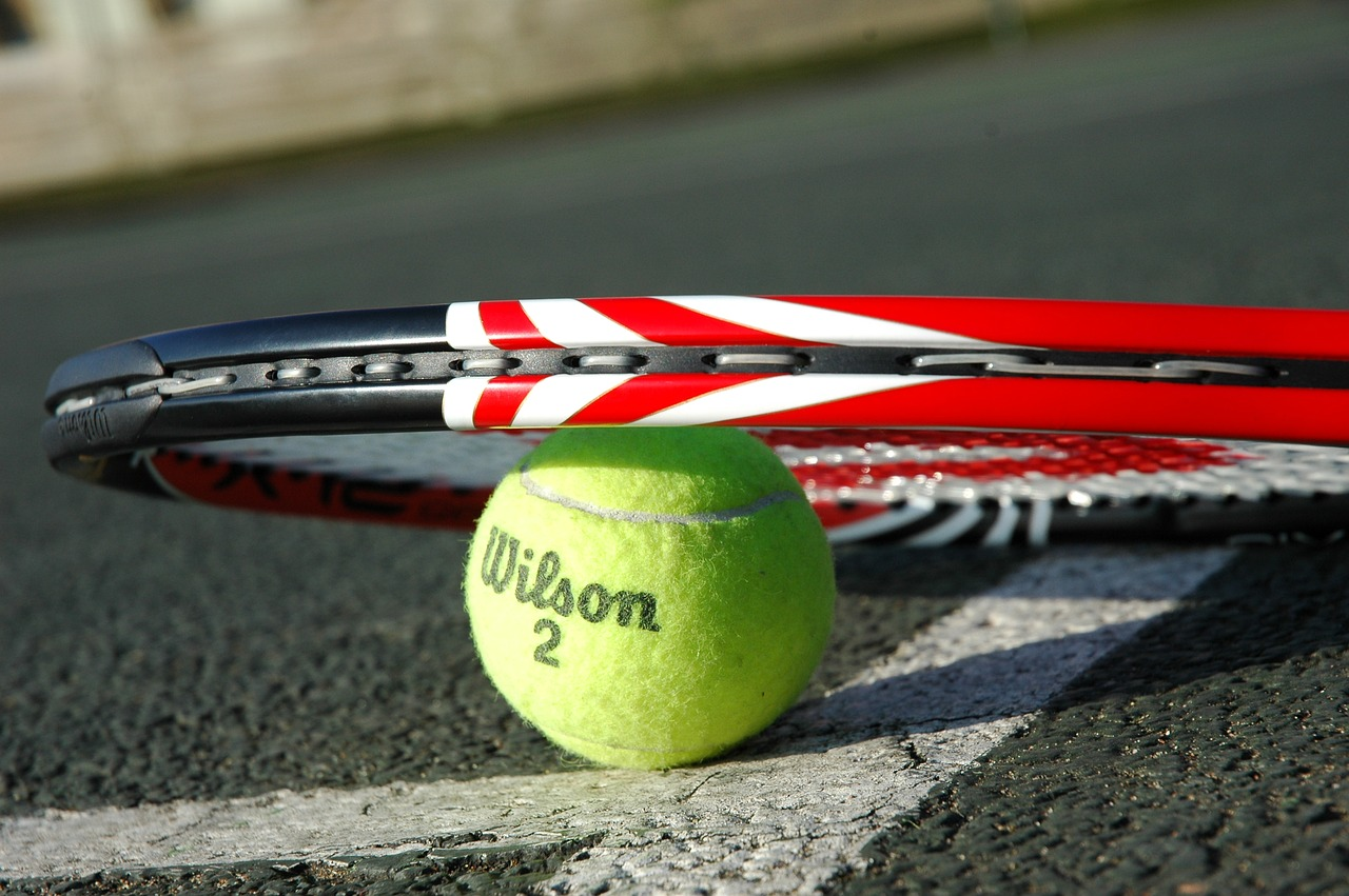 A tennis racket lying on top of a tennis ball on the court.