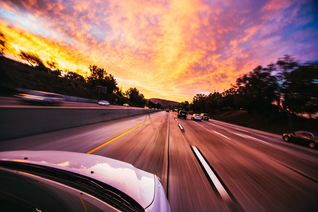 A car driving along an expressway at sunset.