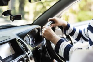 Person wearing a blue and white striped shirt with their hands on the wheel of a car.