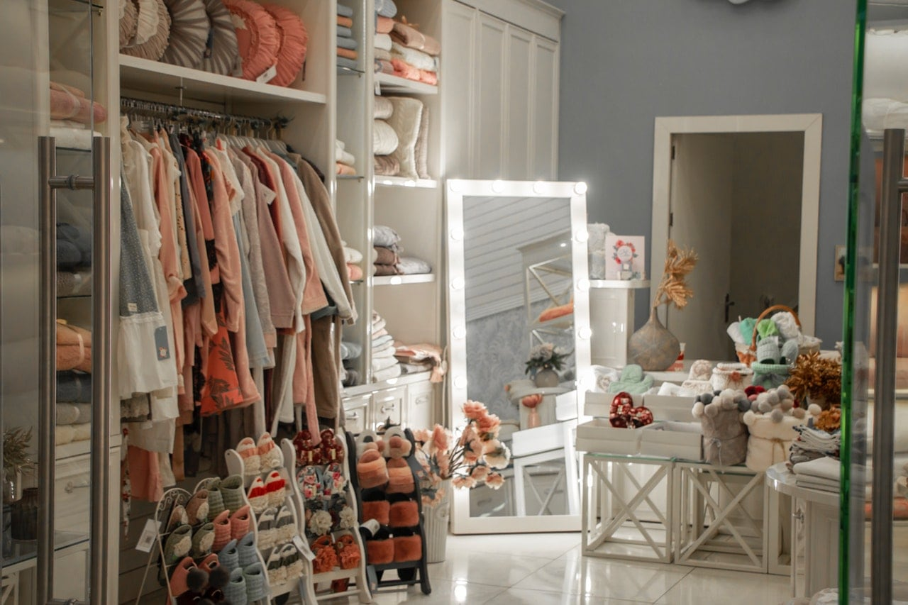 A woman's bedroom filled with clothes, shoes, and miscellaneous items.