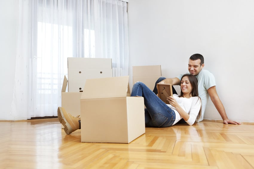 A couple sitting down in their new home, surrounded by unpacked boxes.