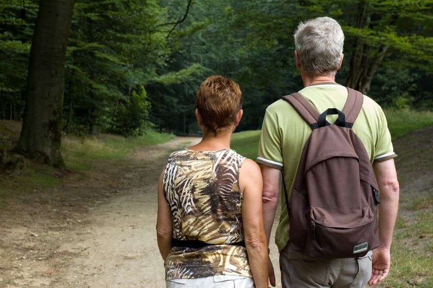 An older couple looking ahead at a nature trail.