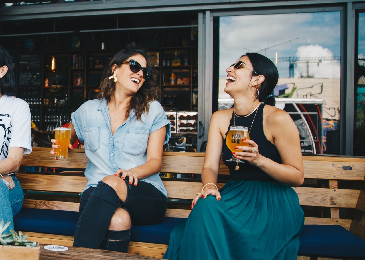 Two women laughing and holding glasses of beer.