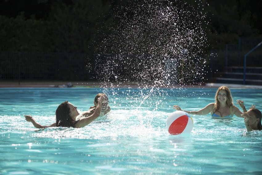 Kids playing in a pool during the summer.