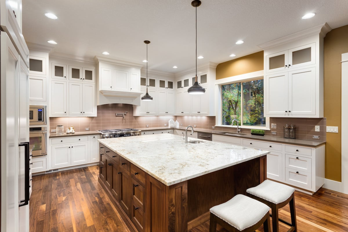 A luxurious kitchen with white cabinets and a huge island centerpiece with white marble.