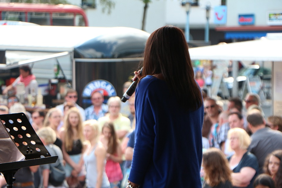 A woman talking on stage at a festival.
