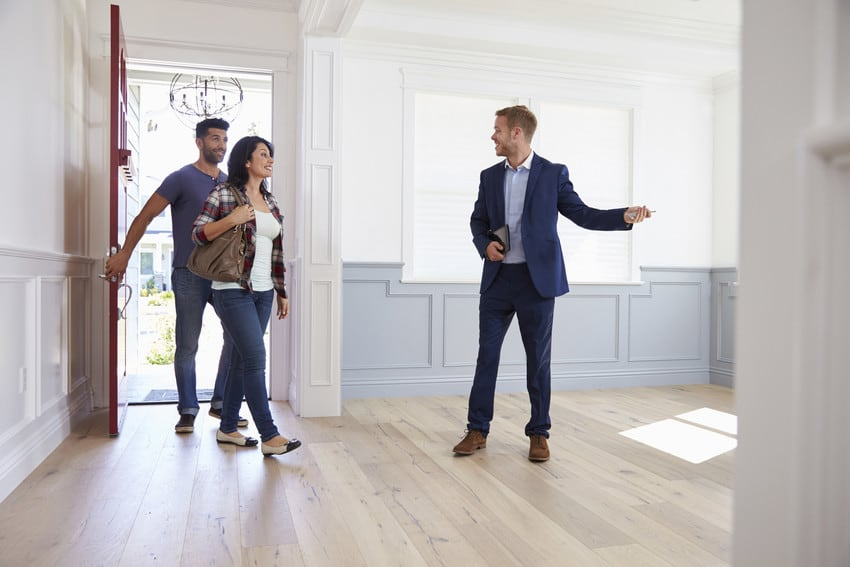 A couple touring a home with a real estate agent.