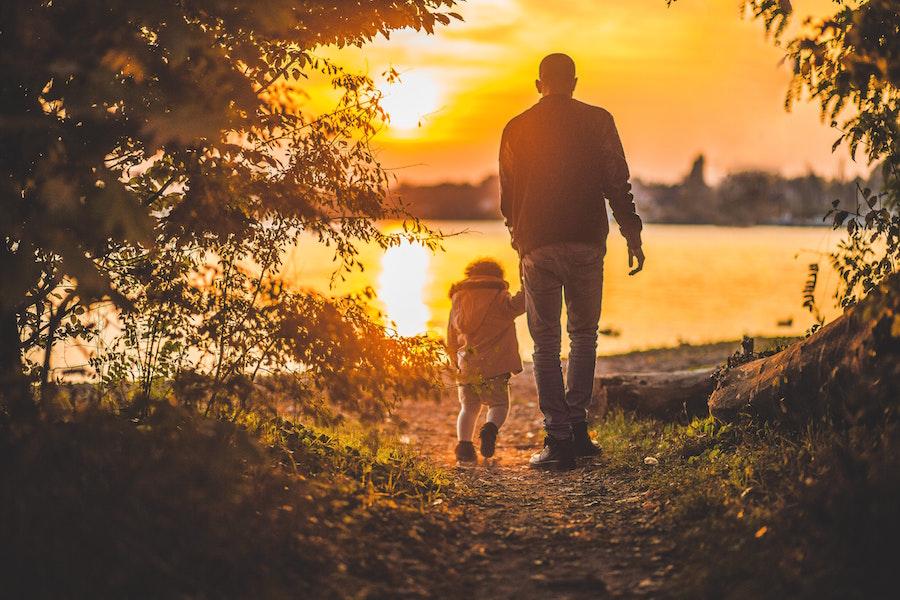 Adult and child enjoying sunset on the lake.