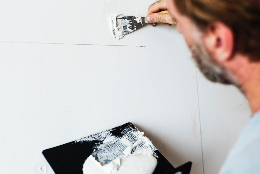 Man making repairs to a wall