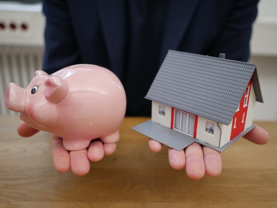 Person holding house and piggy bank
